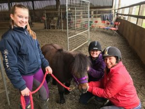 Girl with shetland pony and two Recommended Trainers smiling